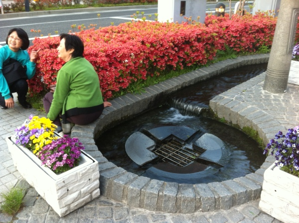 Women posing by flowers and water feature, Matsumoto, Japan, (c) MMD 2013